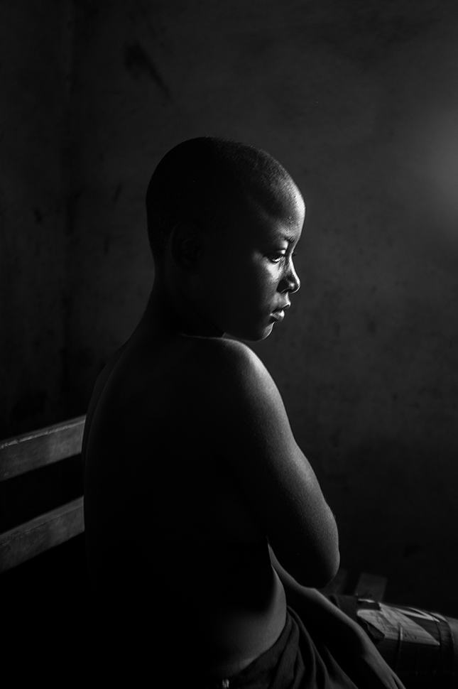 November 2016, Cameroon. Kamini Tontines, 12 years old, is hiding her breasts after having them ironed by her mother. Early marriage, teenage single motherhood, and rape are common in Cameroon. When a girl's breasts start to develop, her mother or grandmother will sometimes heat a stone and massage the breasts to make them disappear so that men will not be enticed by them.