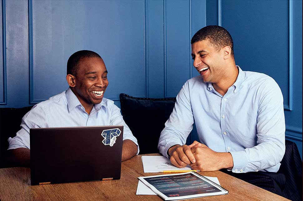 Nnamdi Okike and Aaron Holiday chat in front of a computer