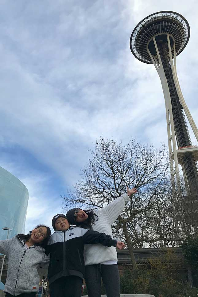 Greg Garcia and his kids pose for a photo beneath the Space Needle in Seattle