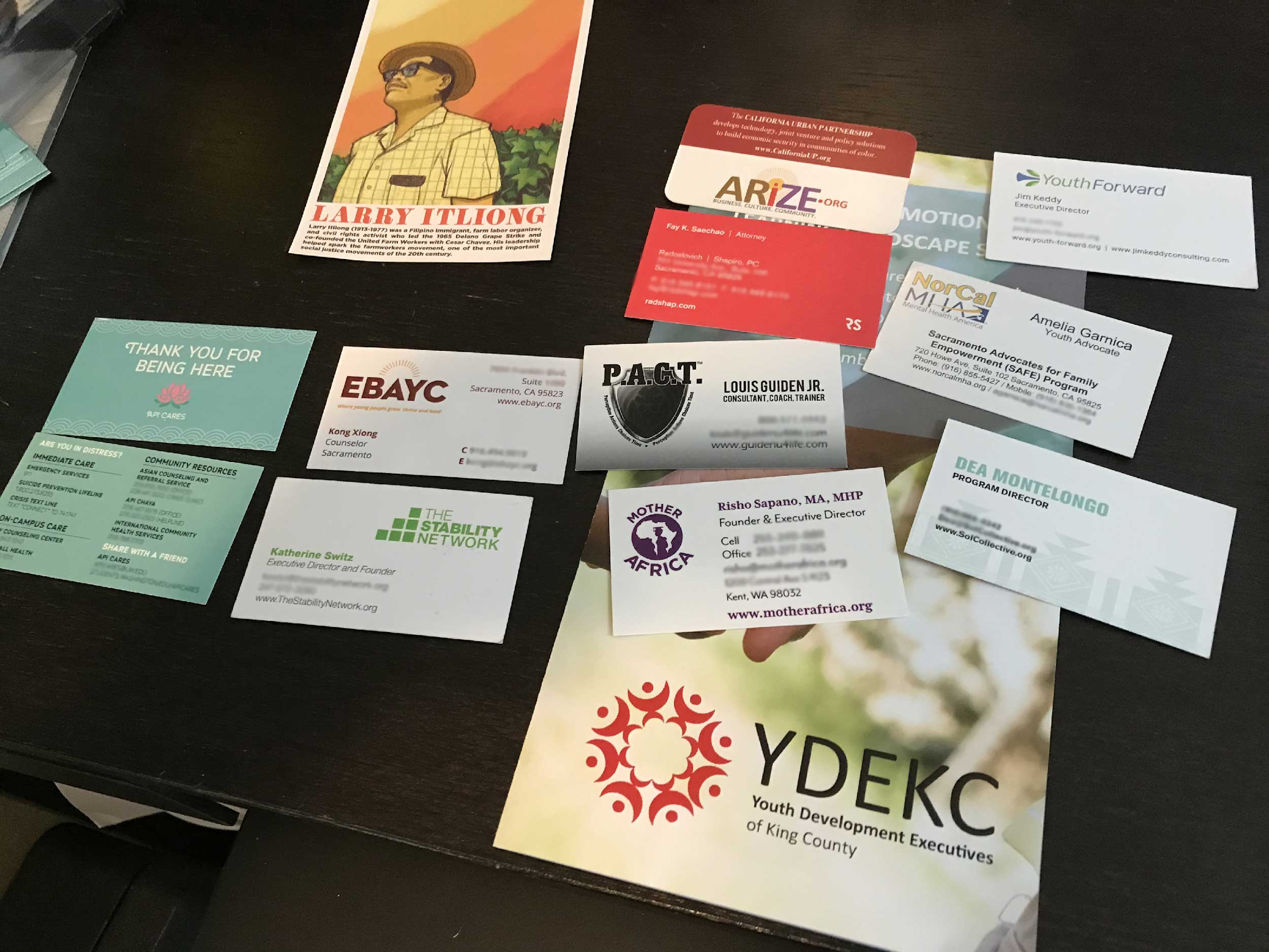 A collection of business cards collected at an event by Greg Garcia lay on a table