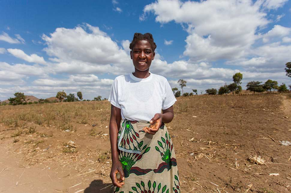 Patricia, a seed grower from Malawi, stands in her field.