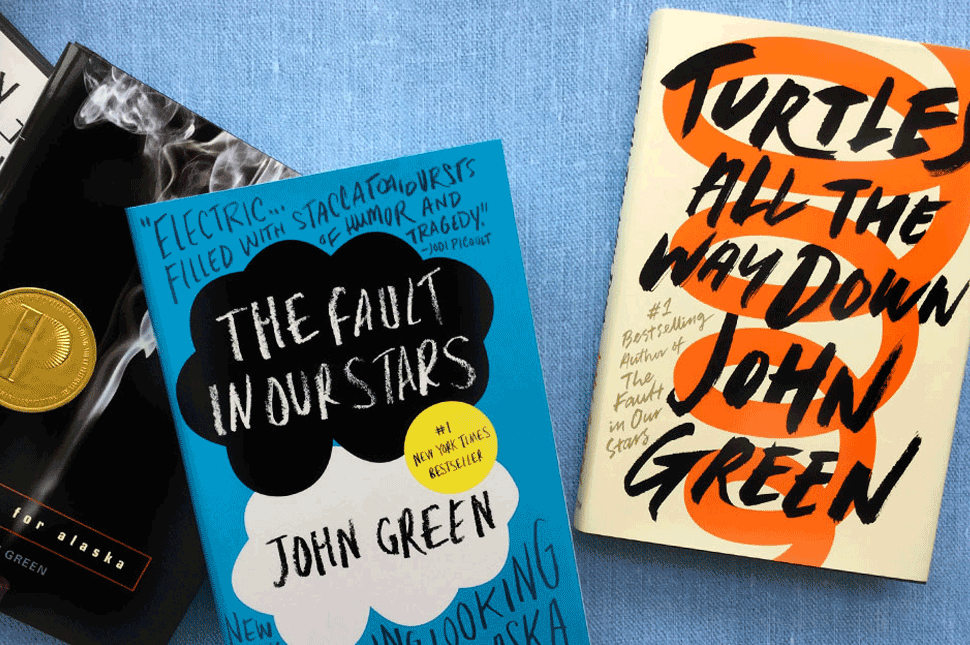 Books written by John Green lay on a blue background