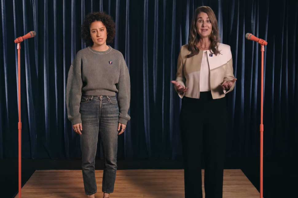 Melinda Gates and Ilana Glazer stand behind two microphones riffing on why it will take 208 years to achieve gender equality