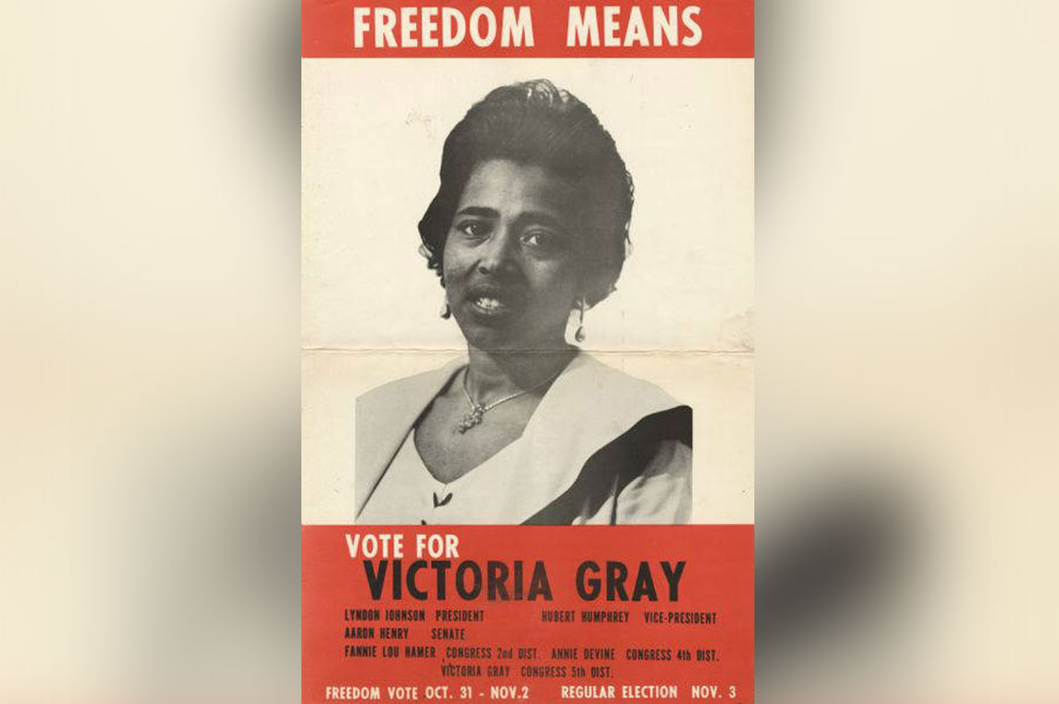 """A poster reads """"Freedom means vote for Victoria Gray,"""" with her photo"""