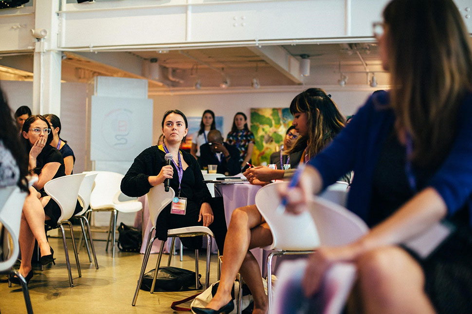A group of teenage women sit around tables asking questions during a headstream event