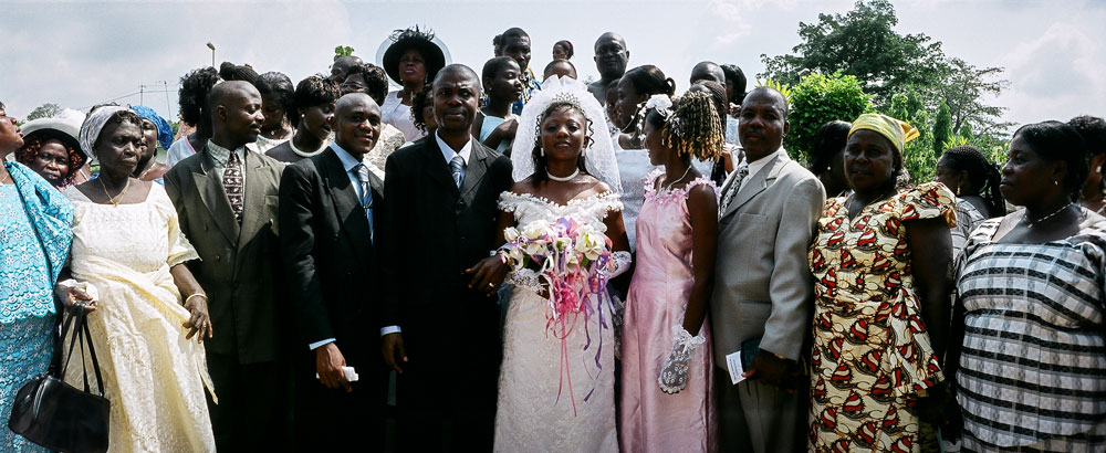 Two families gather for a formal wedding shot outside a church in Akosombo, Ghana