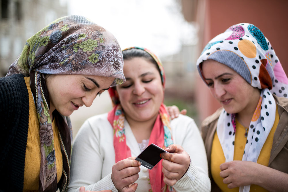 Three Kurdish women look at a polaroid picture of themselves and laugh