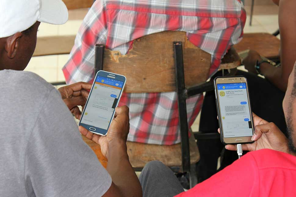 Two men interact with the LucyBot Facebook chatbot in Kenya