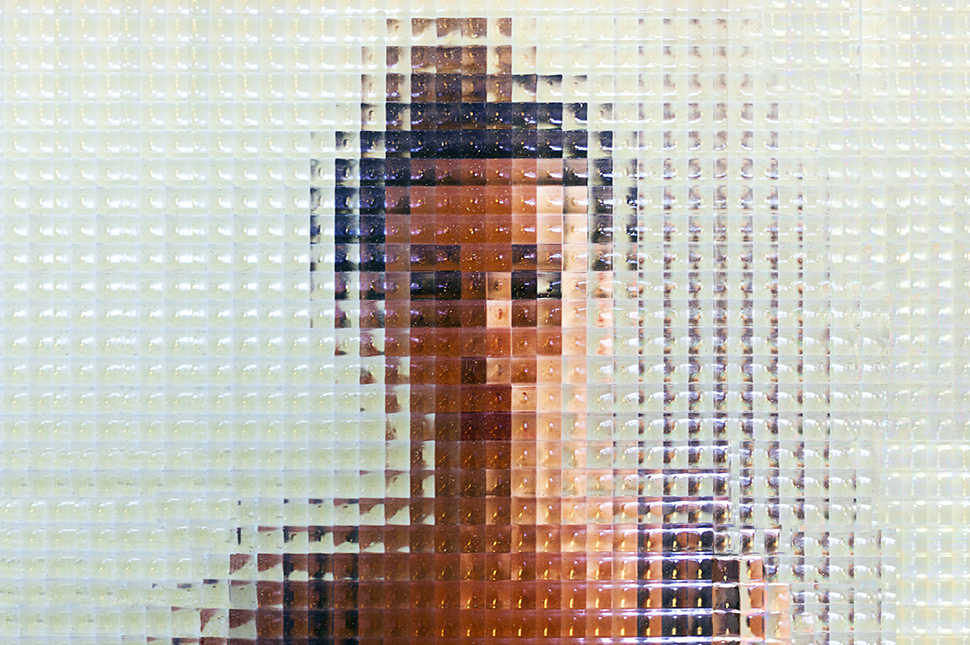 A woman stands behind a checkered glass wall, her image blurred and distorted by the pattern.