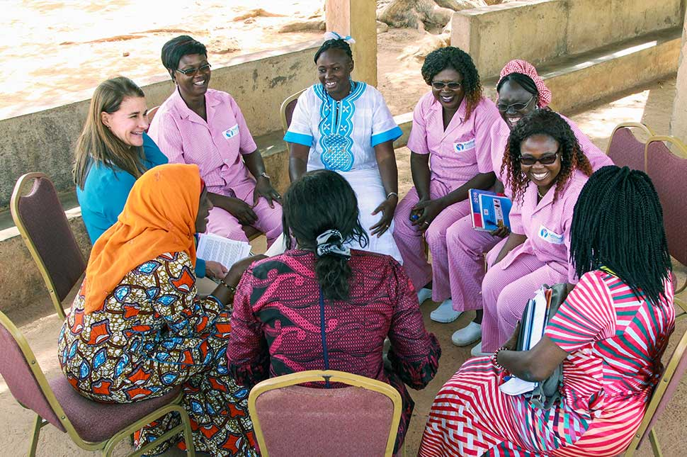 Melinda Gates sits in a circle with women in Africa.