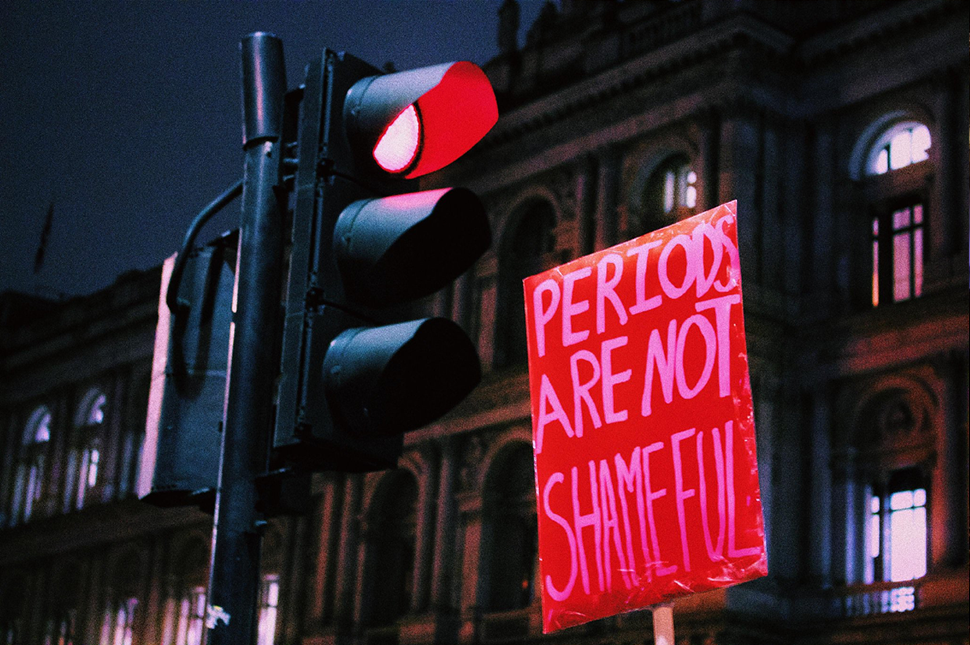 A poster next to a stoplight at the #FreePeriods march in London.
