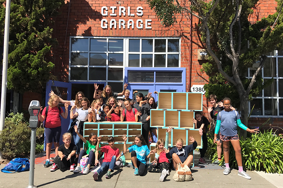 Girls stand in front of the brick-building home of Girls Garage along with their projects.