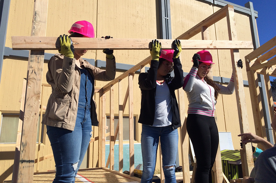 Three girls wearing hard hats hold a wooden beam on their shoulders.