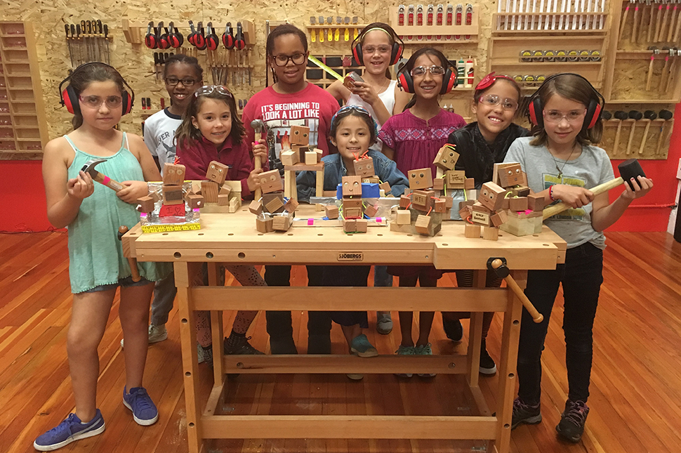 Girls from Girls Garage stand with hammers and mallets next to wooden-block robots they built.