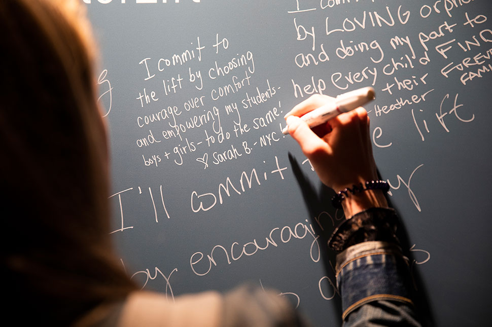 A woman writes on the wall at The Moment of Lift tour event in Chicago