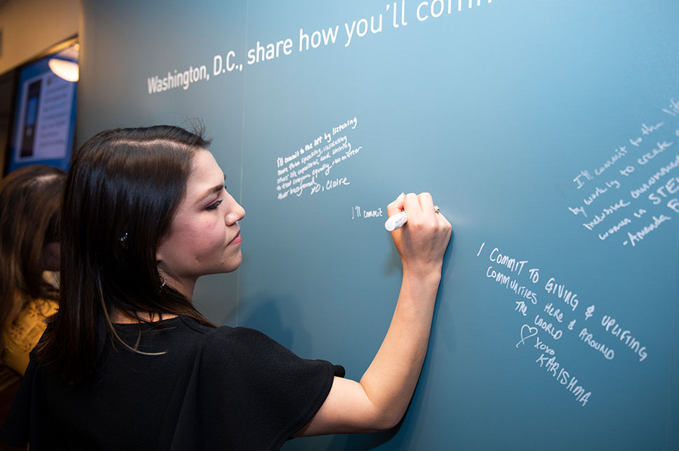 A woman writes her commitment to gender equality on a wall at the Moment of Lift tour event in Washington D.C.
