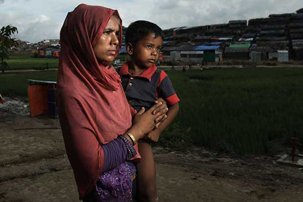 Photo of a mother and her child standing in a field in Bangladesh