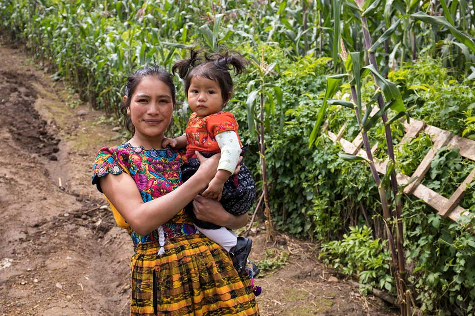A woman stands in front of a farm in Guatemala while holding her baby.