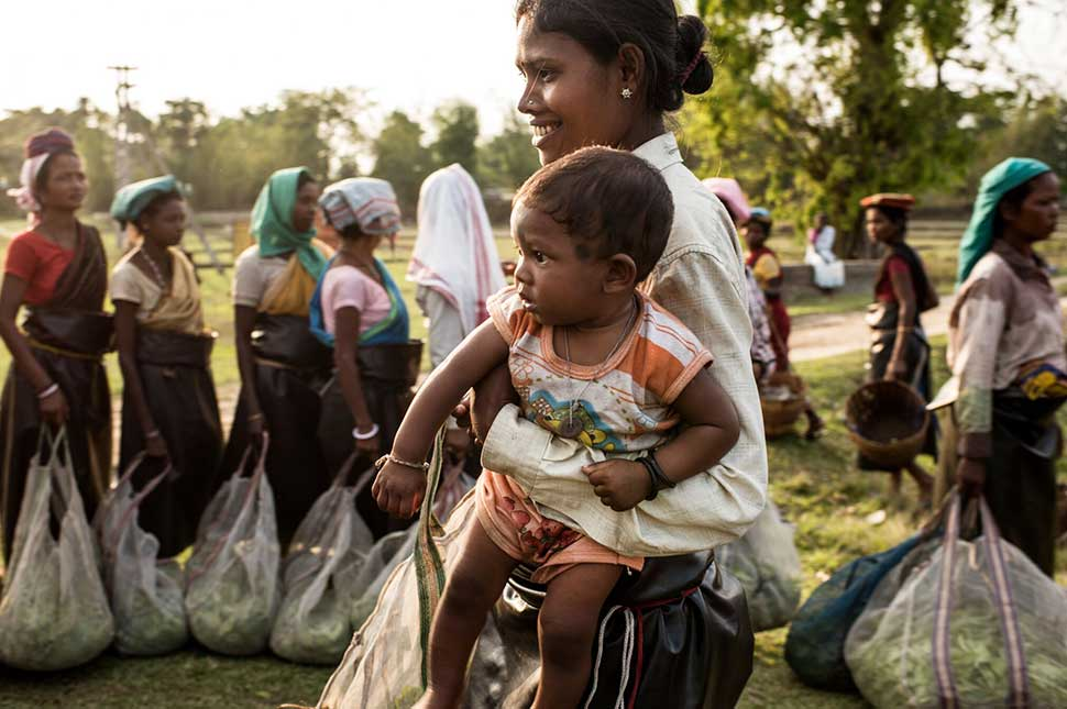 A woman holds her baby in one arm and a bag of produce from the farm she works in India in the other.