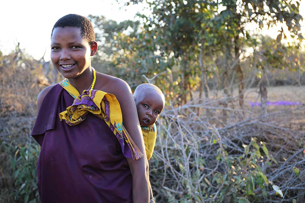 A woman in Tanzania stands in the brush with her baby slung on her back.