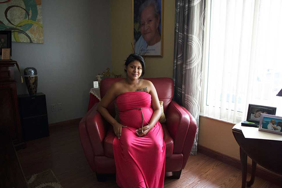 An American woman who is pregnant sits in a red chair in her living room