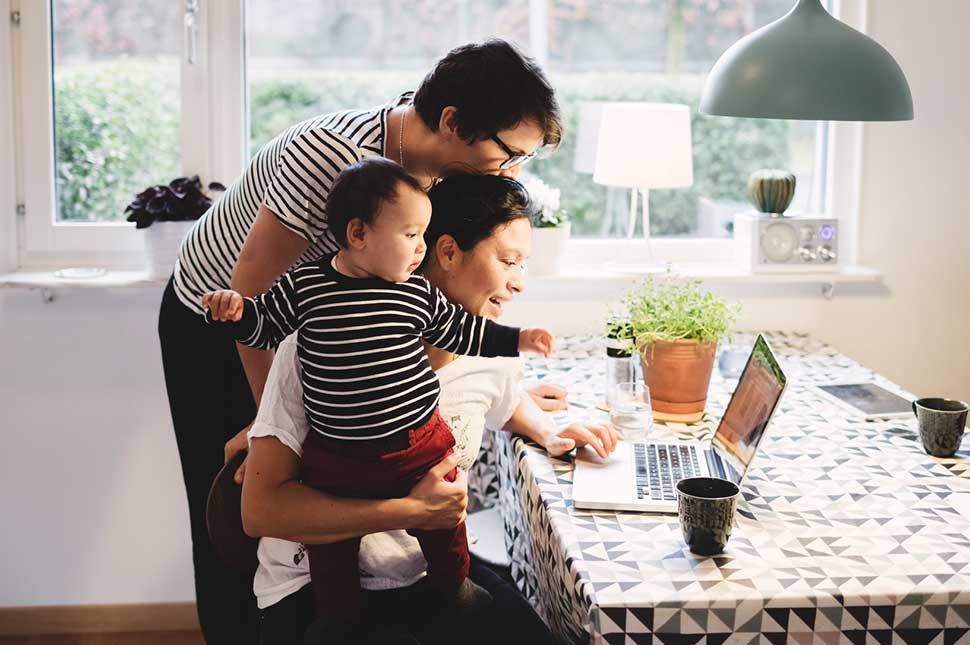 Two women hold their child while sitting at a kitchen table looking at their computer.