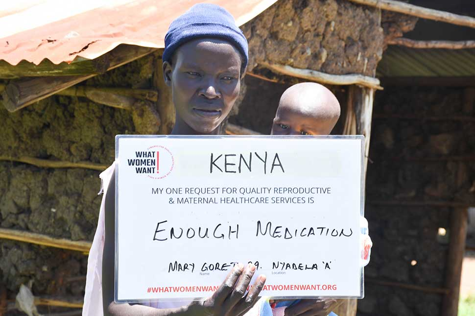 """A woman in Kenya holds both her baby and a sign that reads """"What women want is enough medication"""""""