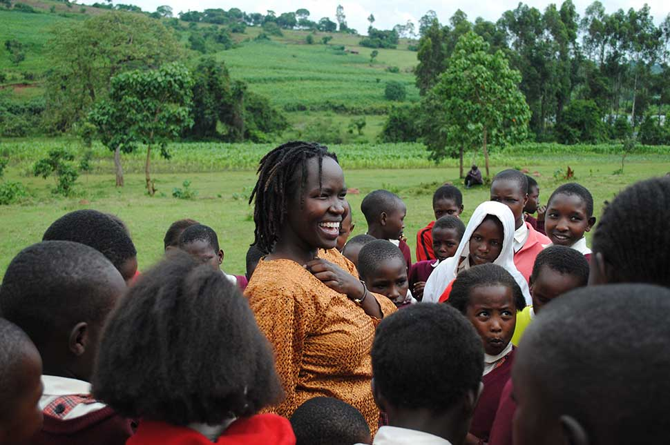 Kakenya Ntaiya stands surrounded by a group of children from her organization, Kakenya's Dream