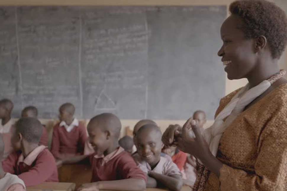 Kakenya Ntaiya stands in a classroom where students from Kakenya's Dream are studying.