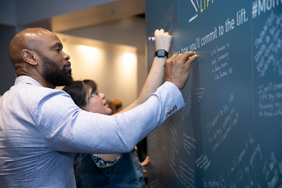 A man and woman sign their commitments to gender equality at the Moment of Lift tour event in Nashville