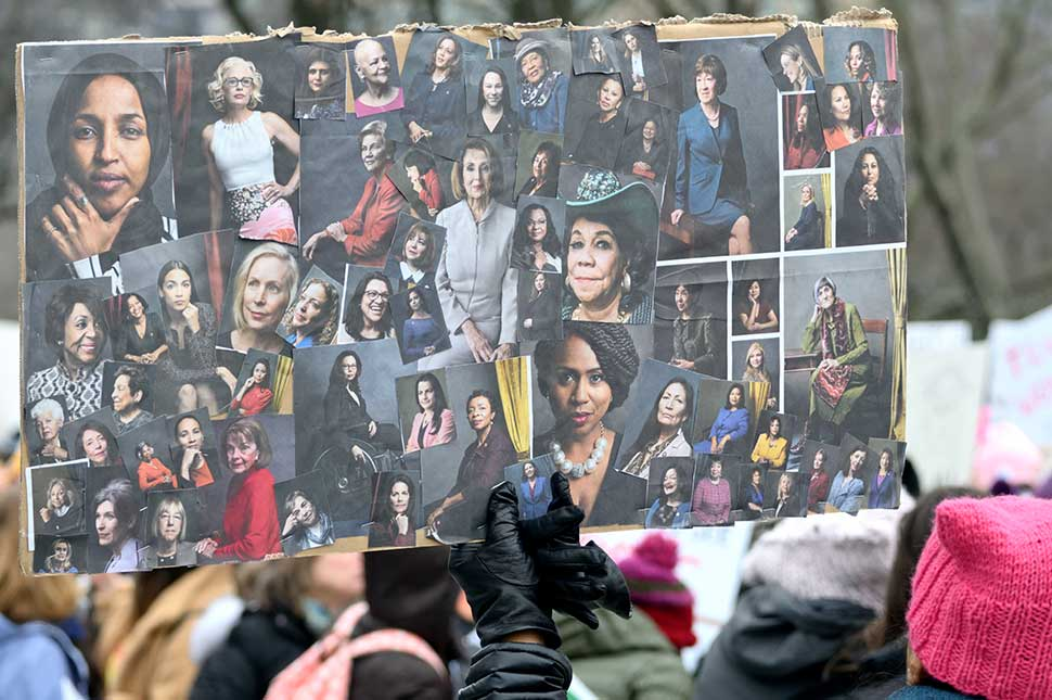 Women at the Women's March hold up a poster showing portraits of strong women