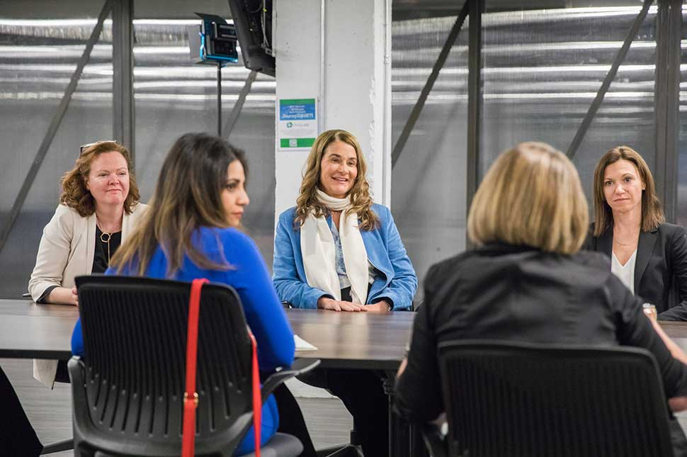 Melinda Gates sits in a board room speaking to the directors of 1871