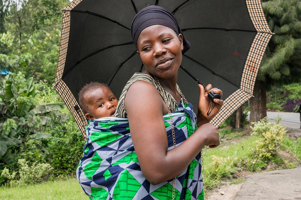 A woman carries her child in a sling on her back while holding an umbrella