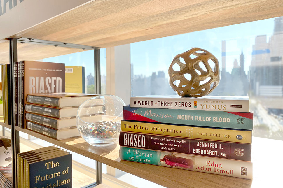 A stack of books sit on a shelf with New York City in the background. The 5 books were recommended to inspire people who want to change the world.