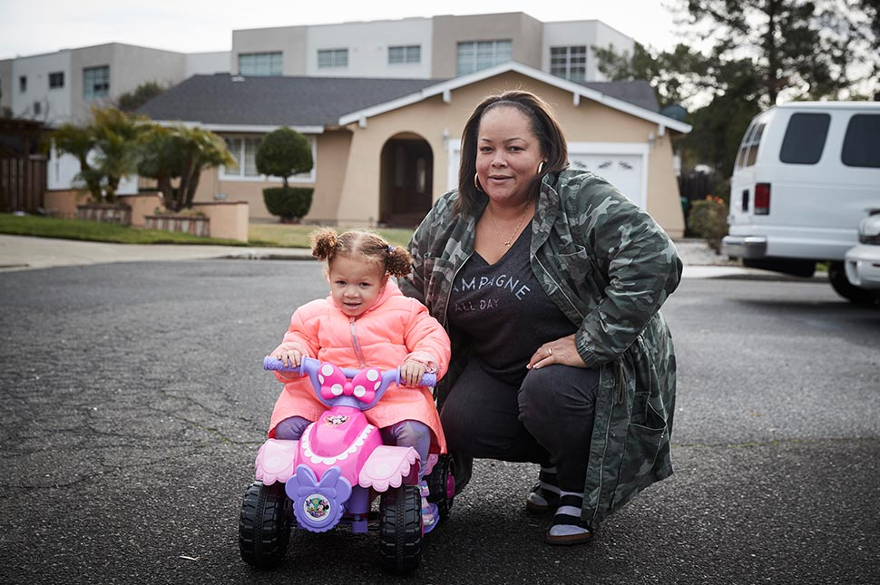 Anita crouches in her cul de sac with her daughter, who is riding a toy bike