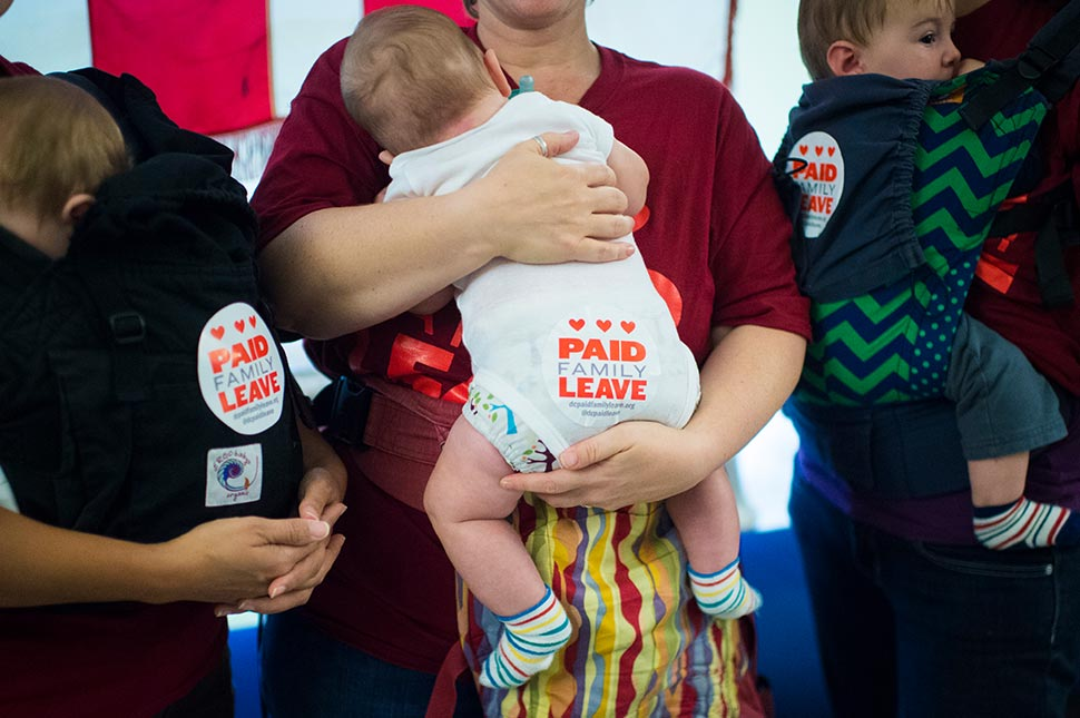 "A woman holds her baby in the hallway after showing support for a paid family leave bill in D.C. The baby's onesie has a sticker on the bottom that reads ""Paid Family Leave"" with three hearts above it."