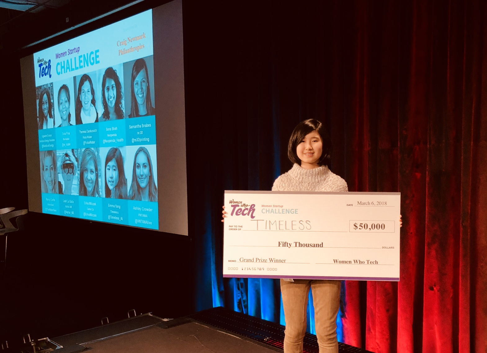 Emma Yang stands on stage holding a check for $50,000 that she won at the Women Who Tech startup challenge in 2018