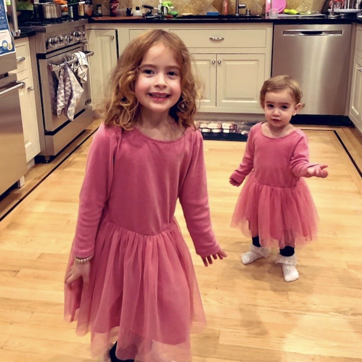 Sara Mauskopf's (founder of caregiving startup Winnie) two daughters wearing matching pink outfits with frilly skirts posing in their household kitchen.