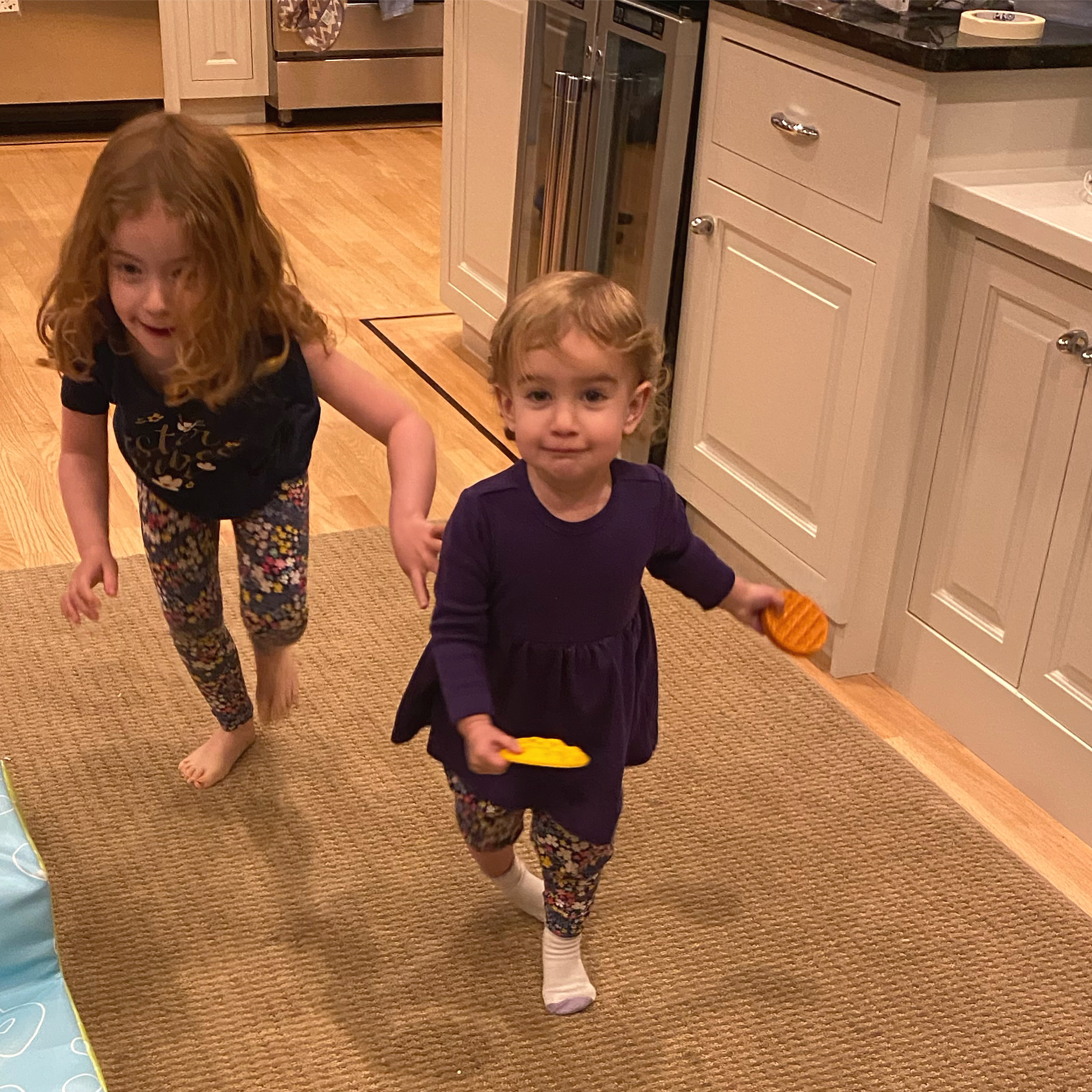 Sara Mauskopf's two daughters run toward the camera through their home's kitchen
