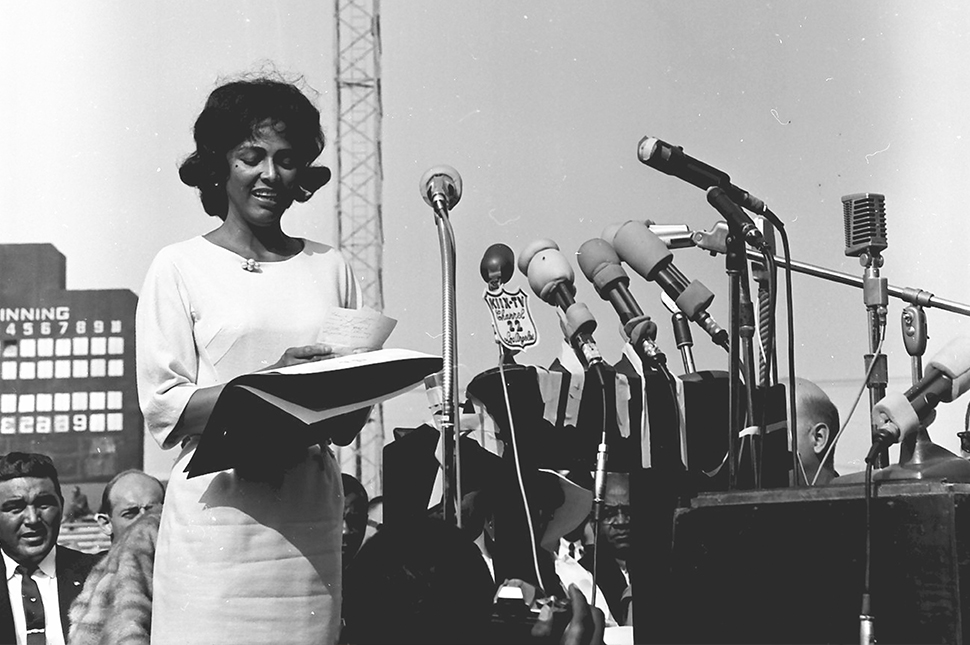 Actress Dorothy Dandridge stands behind a row of microphones  addressing a crowd gathered to hear the Reverend Martin Luther King, Jr. during his first visit to Los Angeles, May 1963
