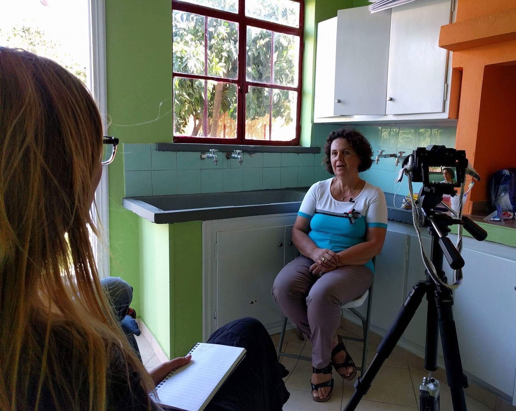 A woman sits in the corner of her kitchen being interviewed. A camera on a tripod is in front of her, with another woman sitting in the foreground holding a notepad.