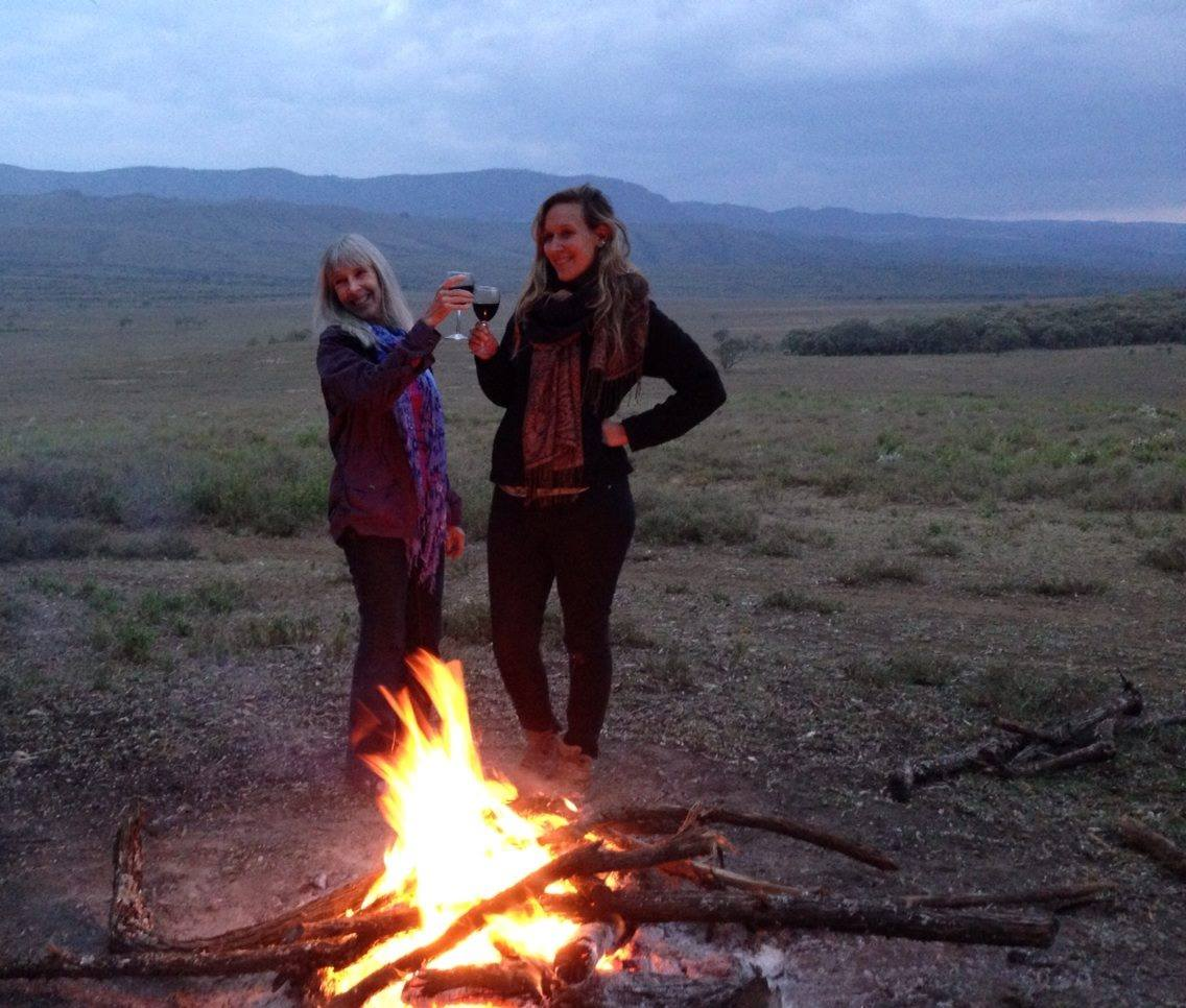 Maggie Lemere and her mother stand behind a bonfire in a valley clinking their wine glasses together.