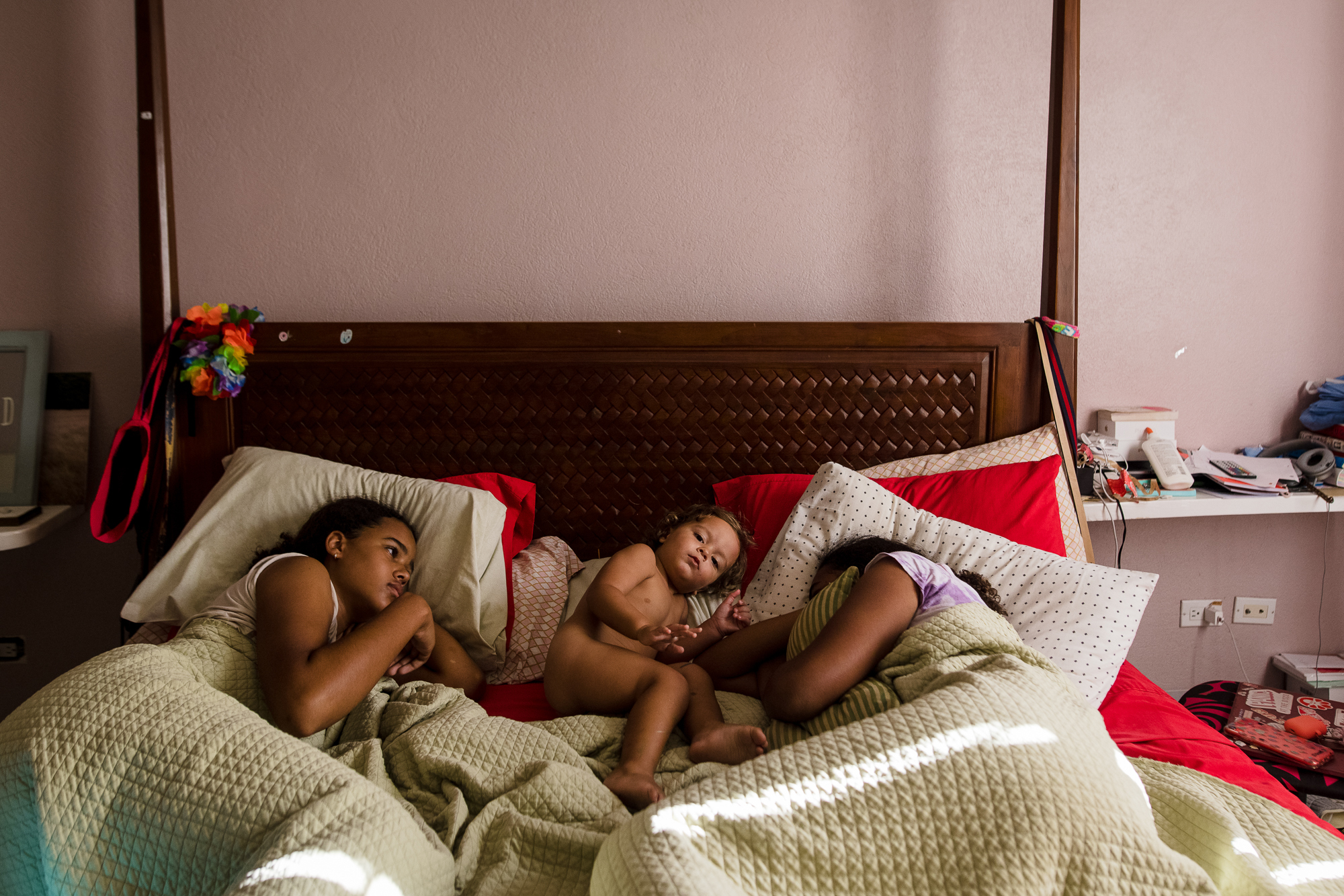 A toddler boy lays on a bed between his two older sisters who are covered in their blanket.