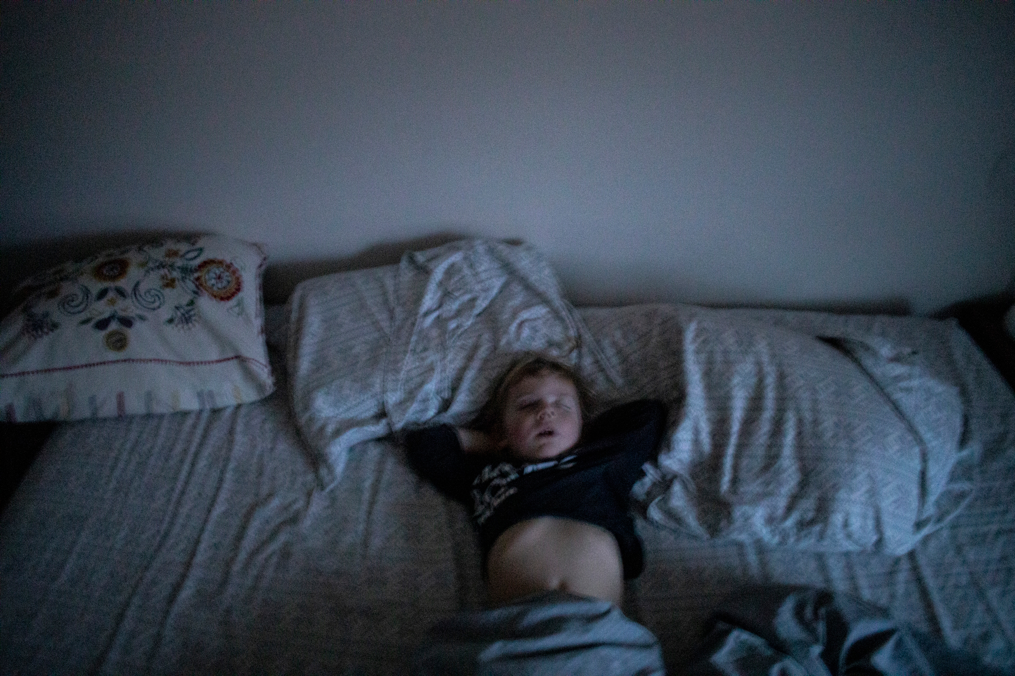 A young boy lays on his back on a bed, asleep with his arms behind his head.