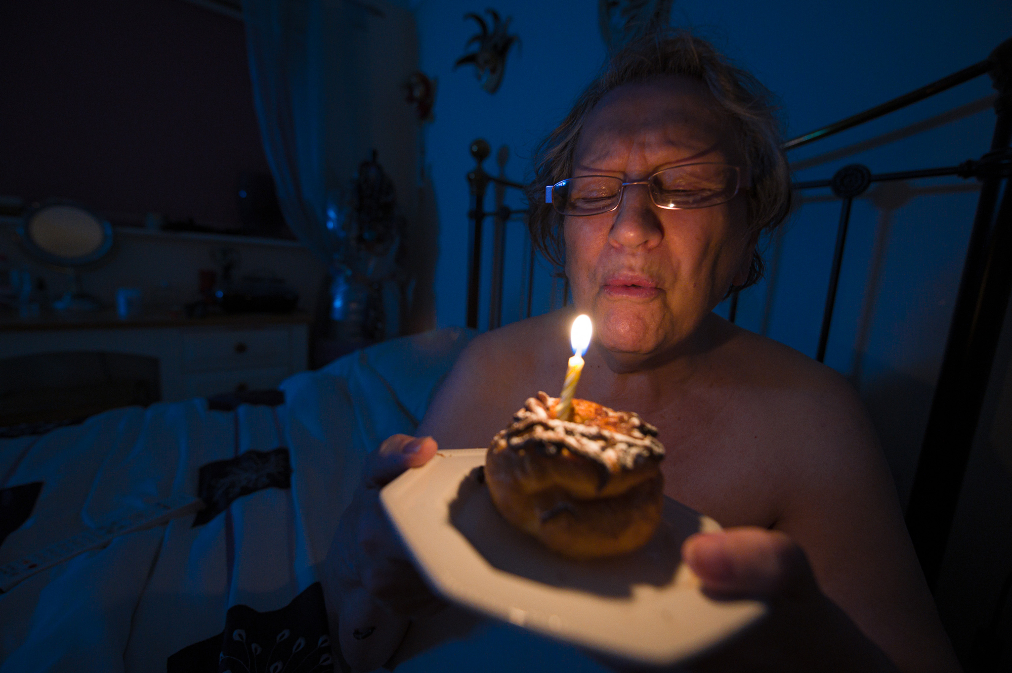 An elderly woman sits on her bed in a dark room, blowing out a single candle on a plated donut.