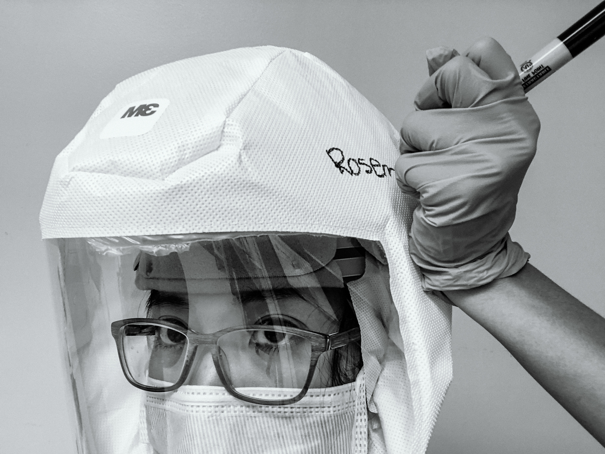 "Using a gloved hand, a nurse in glasses writes ""Rosem"" with a sharpie on her hooded and shielded personal protective equipment."