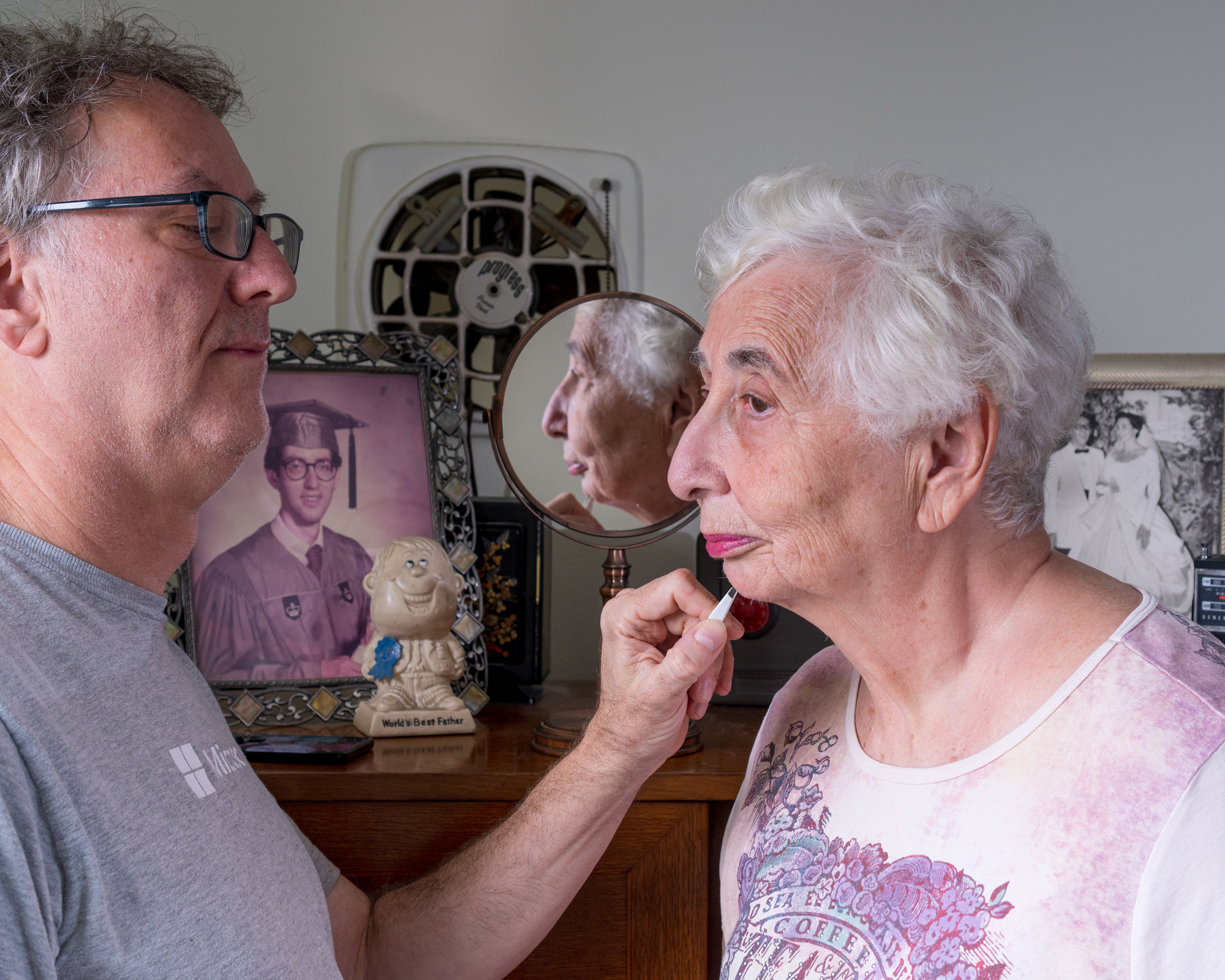 An adult man assists his elderly mother with her beauty routine in her home. An old portrait of a man in a graduation cap, a black and white wedding portrait, and a mirror sit on a dresser behind them.