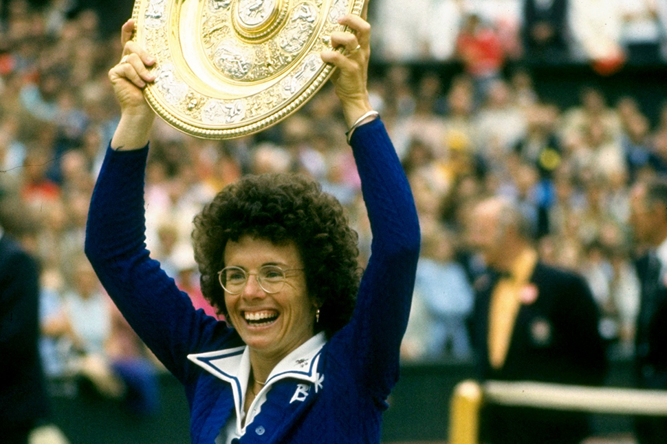 Billie Jean King holds up a circular plate trophy after winning Wimbledon in 1975
