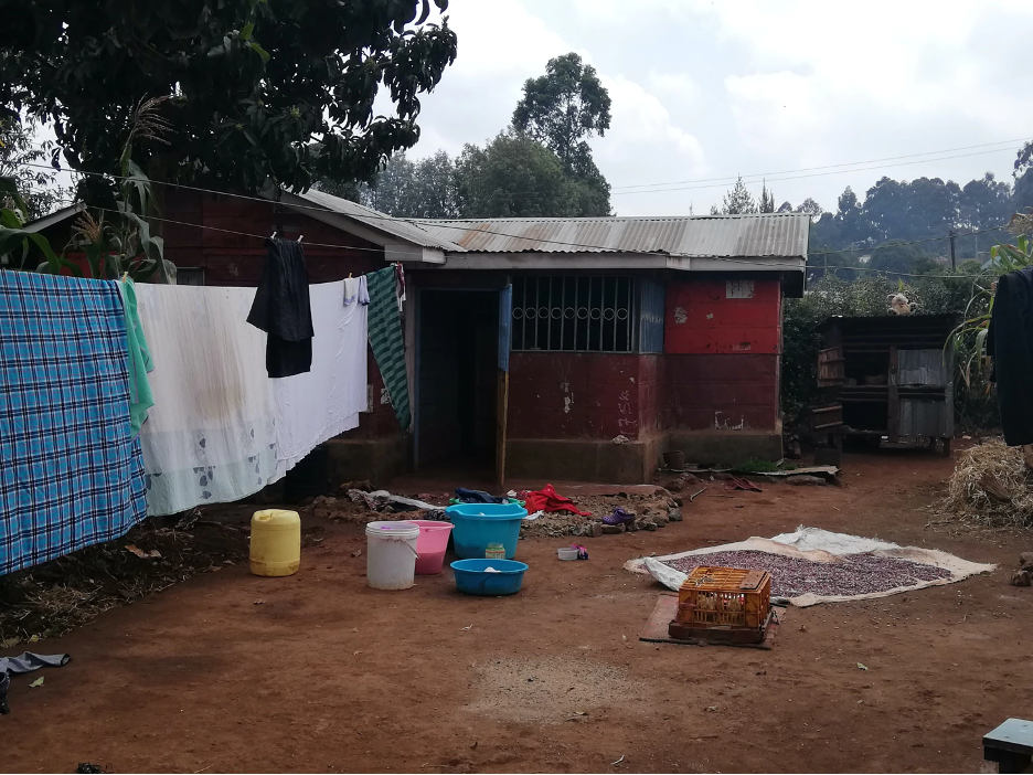 A courtyard in a Kenyan home has a tin-walled shack in the background with a laundry line extending from the corner of the roof.