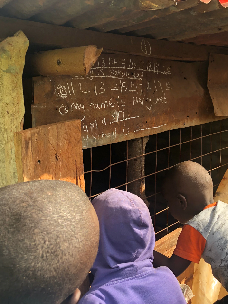 Children sit and look at a blackboard hanging above a chicken coop.
